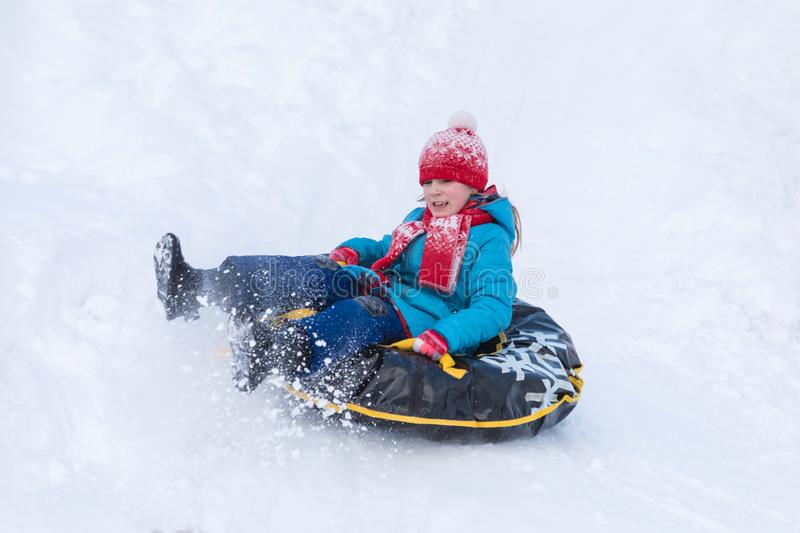 The girl in blue clothes with red hat and scarf descending from the hill covered with a snow on the black rubber ring instead of s royalty free stock photography