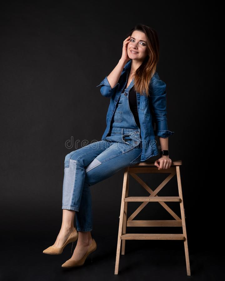 Girl in blue denim suit sitting on wooden step stock image