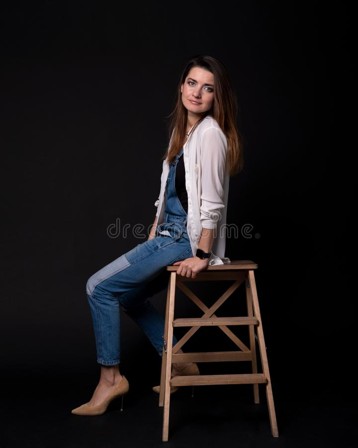 Girl in the blue denim suit with a white pullover sitting on the wooden steps stock image