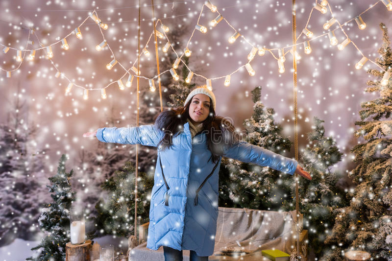 Girl in blue down jacket rejoicing because of snowing standing n stock photography