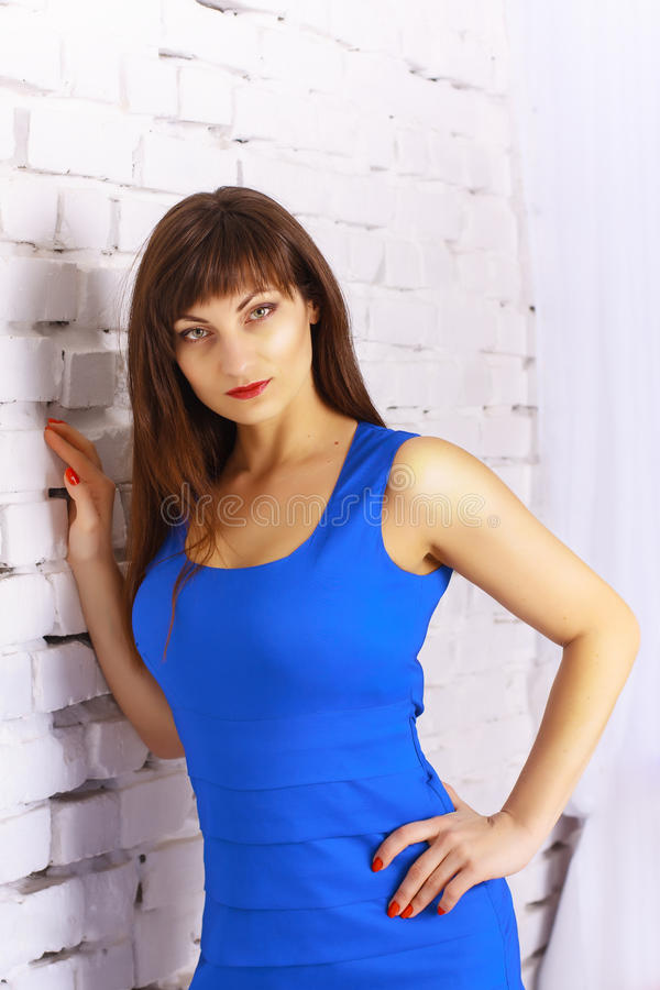 Girl in a blue dress. Beautiful girl in a blue dress on a background of a white brick wall royalty free stock image