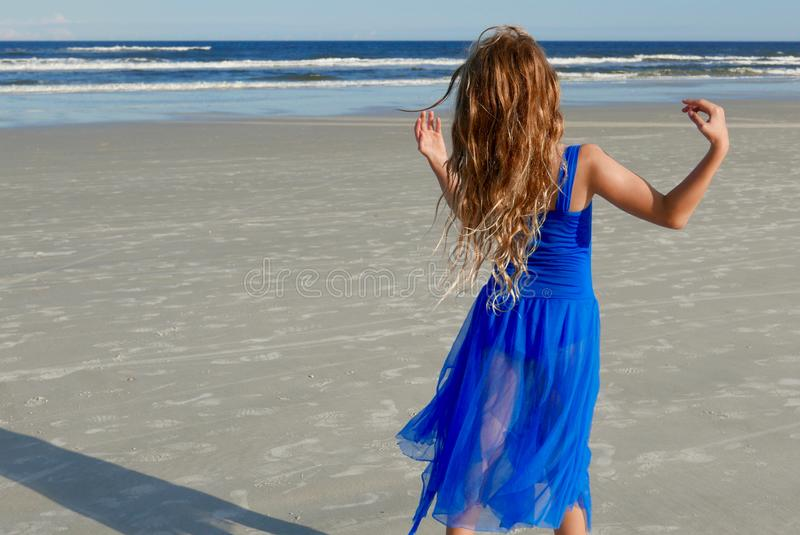 Girl in a blue dress dancing on the beach in front of the ocean stock photography