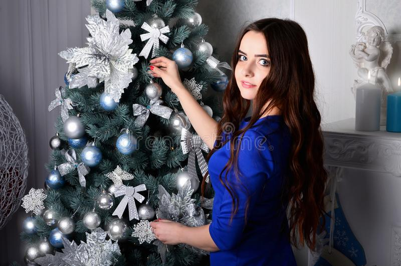 Girl in a blue dress decorates a Christmas tree royalty free stock photos