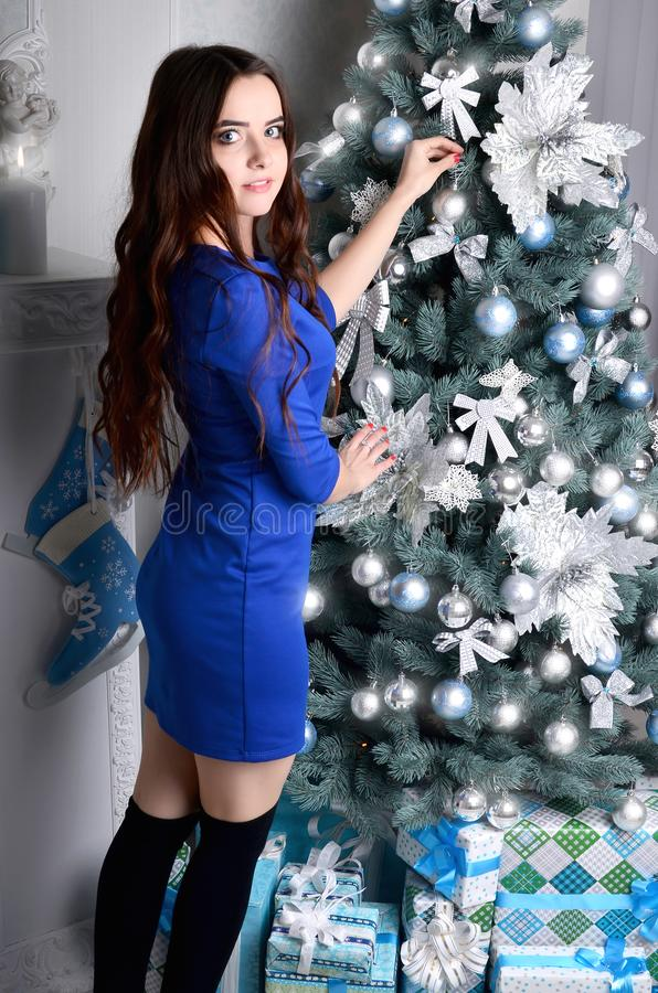Girl in a blue dress decorates a Christmas tree stock photo