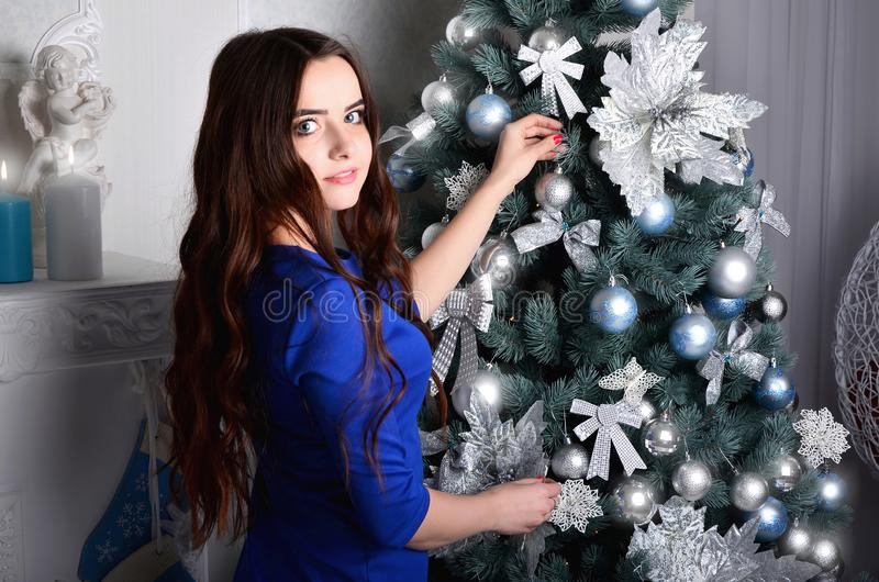 Girl in a blue dress decorates a Christmas tree stock image