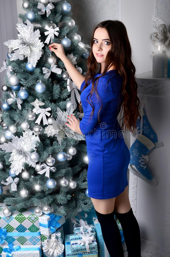 Girl in a blue dress decorates a Christmas tree royalty free stock image