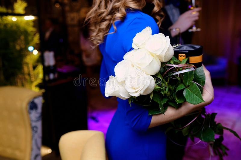 Girl in a blue dress holding white roses  in a restaurant stock photography