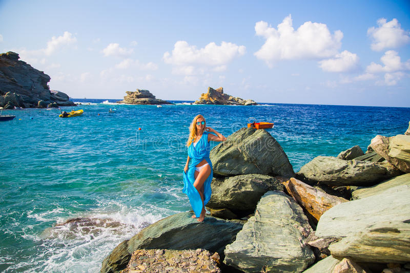 Girl in blue dress at rocky beach royalty free stock photography