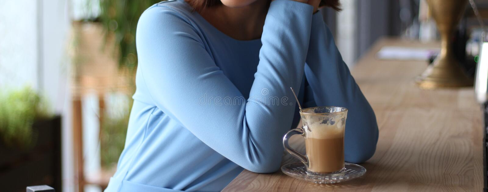 Girl in blue dress sits at a bar counter and drinks coffee.expectation of meeting, meeting. Girl in blue dress sits at a bar counter and drinks coffee royalty free stock image