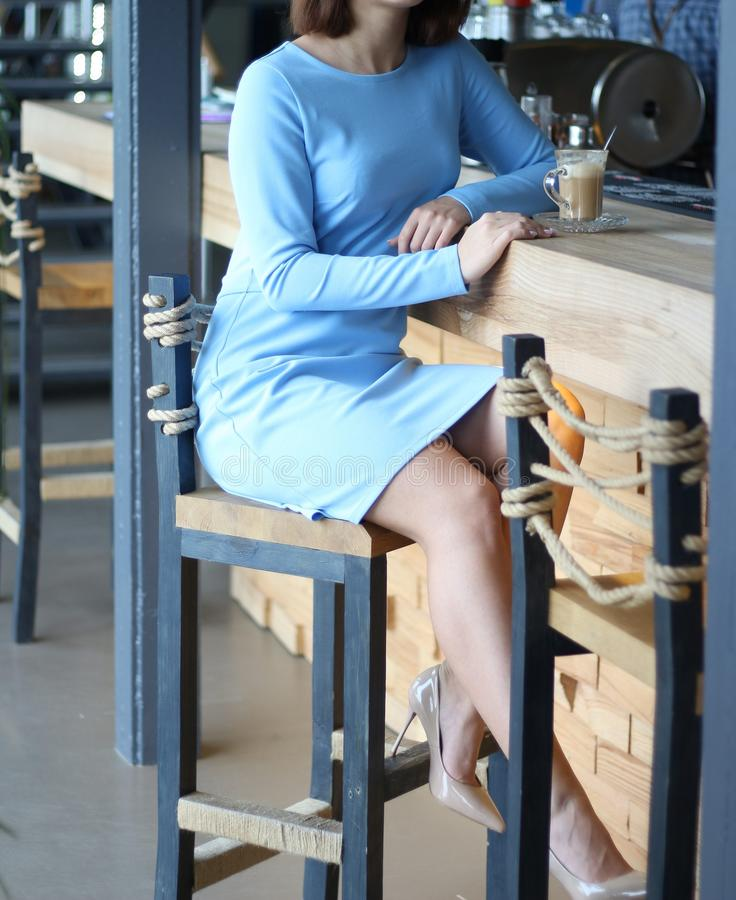 Girl in blue dress sits at a bar counter and drinks coffee.waiting for a meeting, a cup of coffee is on the bar.vertical image. Girl in blue dress sits at a bar stock images