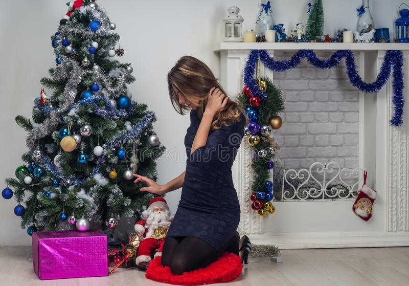 Woman in a blue dress sitting in front of a white decorative fireplace with New Year decorations. Christmas home decoration royalty free stock photos