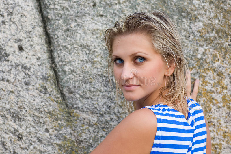 Girl with blue eyes on the background of rocks. Girl with blue eyes in the striped shirt on the background of rocks royalty free stock photography