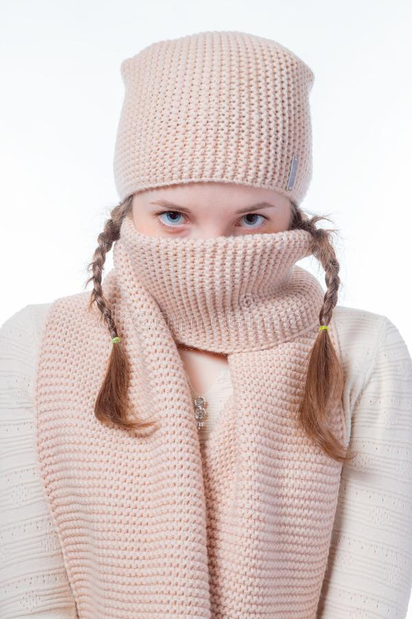 A girl with blue eyes and pigtails hides her face behind a knitted scarf. Gaze into the camera royalty free stock photos