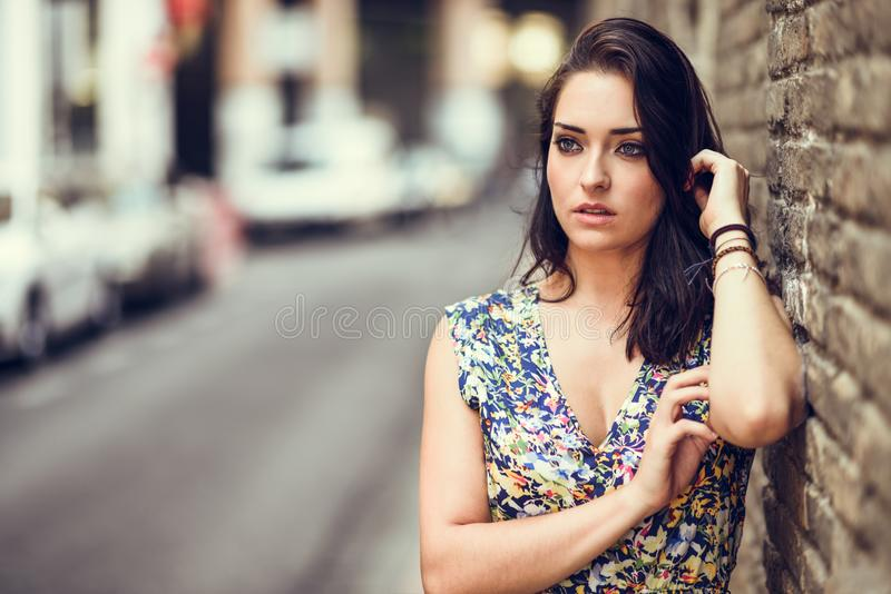 Girl with blue eyes standing next to brick wall outdoors. Young woman in her twenties wearing flower dress in urban background. royalty free stock photo