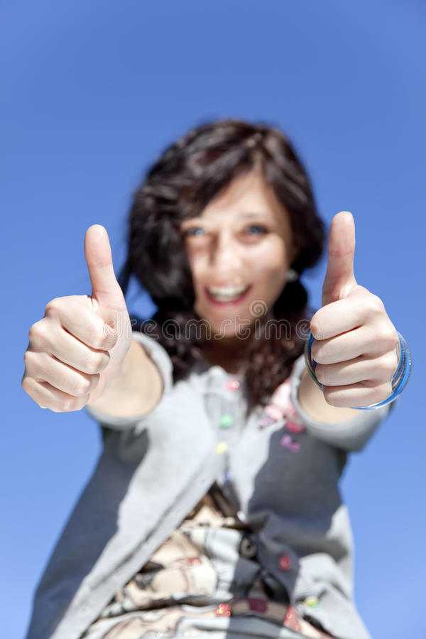 Girl with blue eyes which show hand OK symbol. stock image