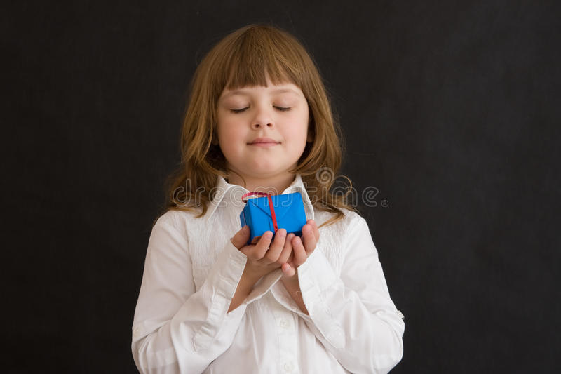 Girl with blue gift. Little girl with blue present on black background royalty free stock images