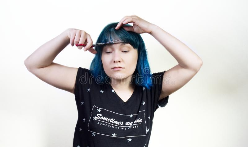 The girl in blue hair cuts her bangs. Studio photo royalty free stock image