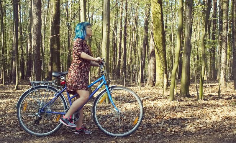 The girl in the dress rides a bicycle through the forest. The girl with blue hair in the dress rides a bicycle through the forest royalty free stock photos
