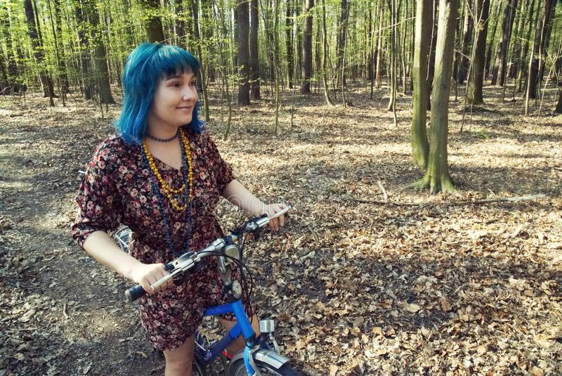 The girl in the dress rides a bicycle through the forest. The girl with blue hair in the dress rides a bicycle through the forest stock photography