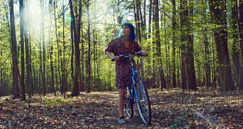 The girl in the dress rides a bicycle through the forest. The girl with blue hair in the dress rides a bicycle through the forest stock images