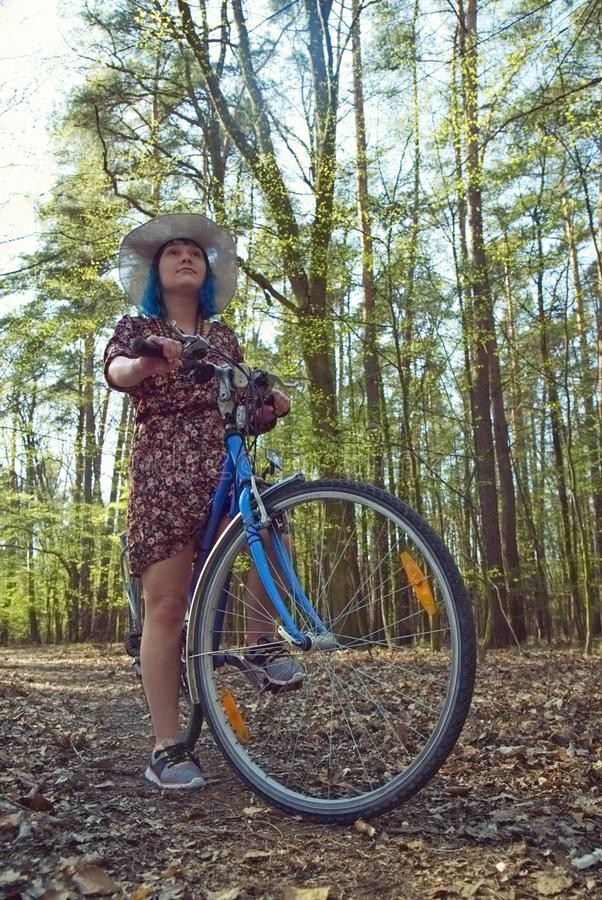 The girl in the dress rides a bicycle through the forest. The girl with blue hair in the dress rides a bicycle through the forest royalty free stock photo
