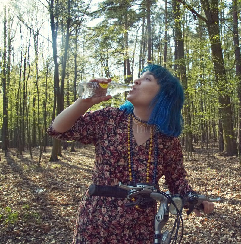 The girl in the forest, on a bike, drinks water from a bottle. The girl with blue hair, in the forest, on a bike, drinks water from a bottle royalty free stock photos