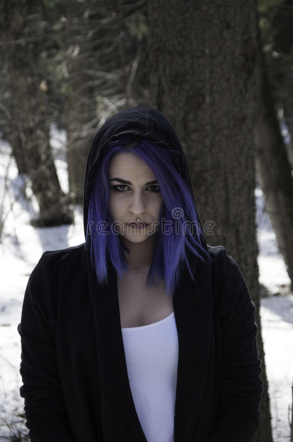 Girl with blue hair in a forest. Girl with blue hair and a pierced lip in a forest stock photos