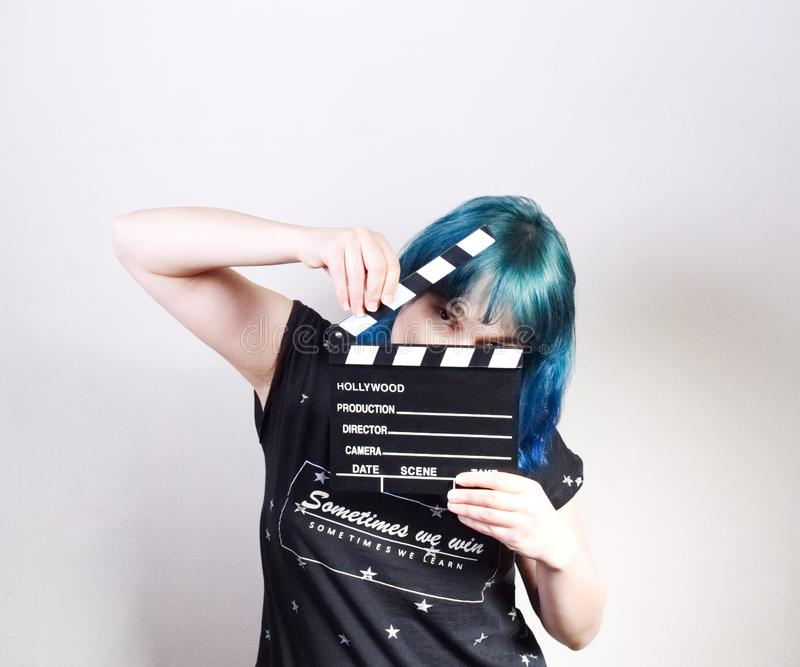 A girl with blue hair, holding a clapper. Picture taken in the studio on a white background stock image