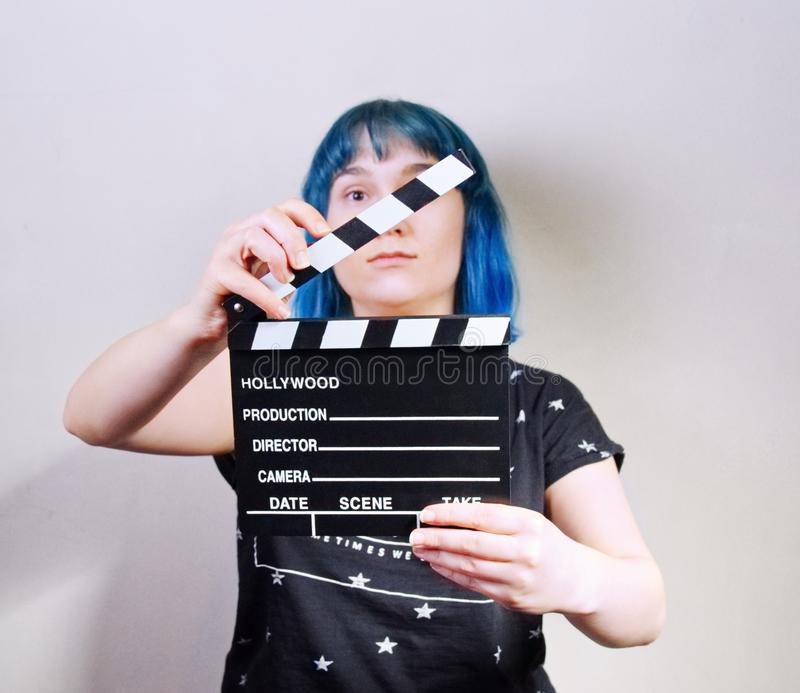 A girl with blue hair, holding a clapper. Picture taken in the studio on a white background royalty free stock images