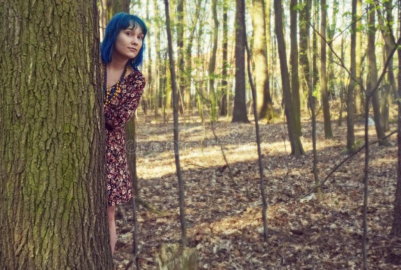 The girl leans out from behind a tree in the forest. royalty free stock images
