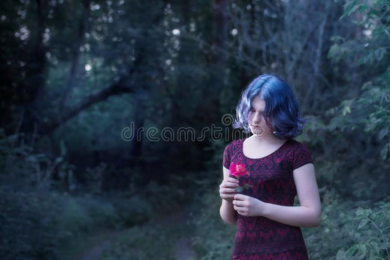 Girl with blue hair in night forest. Beautiful girl with blue hair in night forest stock photography