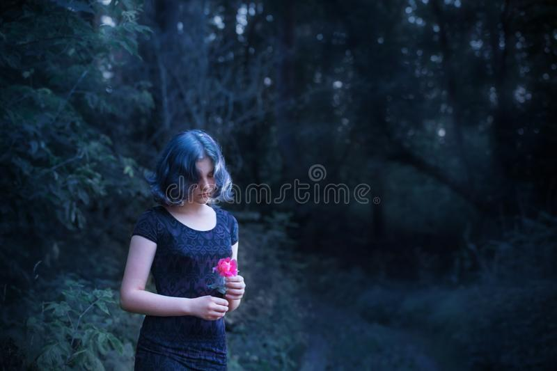 Girl with blue hair in night forest. Sad girl with blue hair and pink rose  in night forest royalty free stock photography