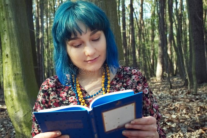 The girl is reading a book in the forest. The girl in blue hair is reading a book in the forest royalty free stock photo