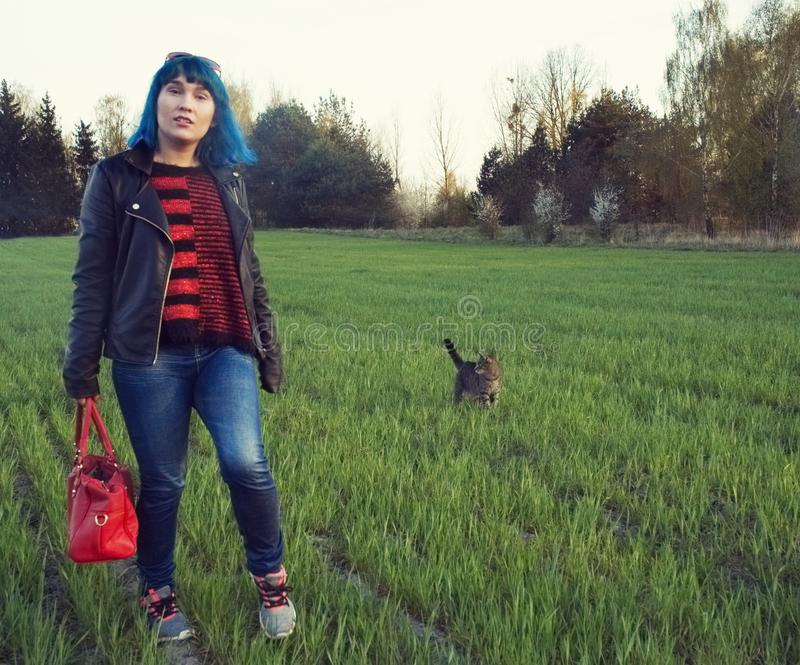 The girl is walking with her cat in the field. The girl with blue hair is walking with her cat in the field royalty free stock images
