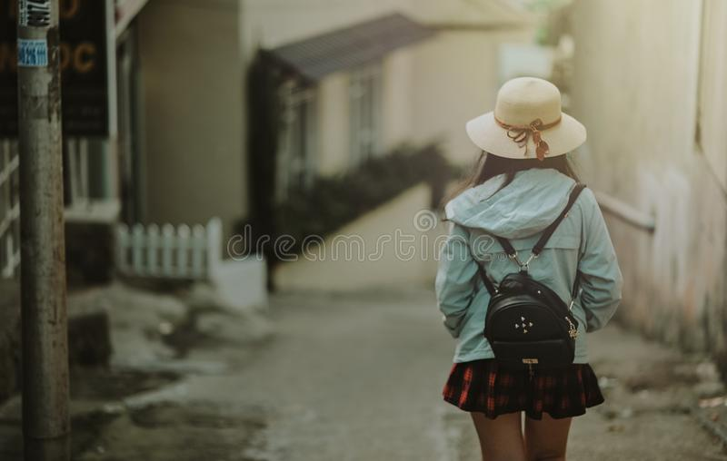 Girl in Blue Jacket and Black Leather Knapsack Walking on Street royalty free stock photo
