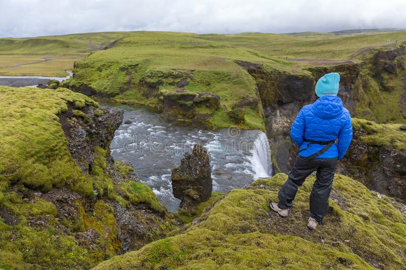 A girl in a blue jacket stands on the edge of a cliff by the Fagrifoss Waterfall royalty free stock image