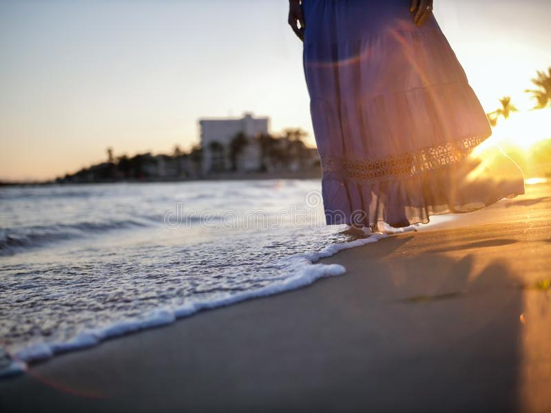 A girl with a blue skirt walks along the beach during sunset stock image