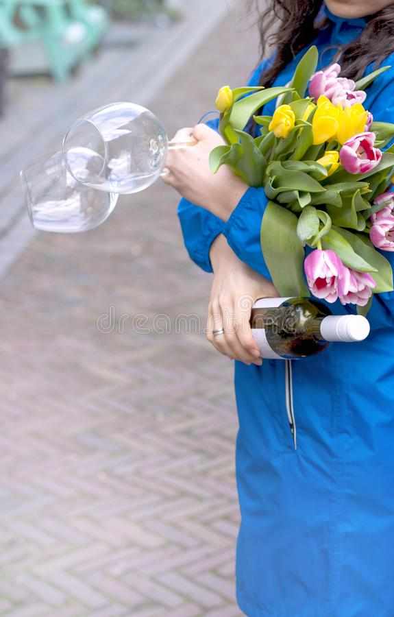 A girl in a blue raincoat on a city street. In the hands of a bottle of red wine and two glasses. A bouquet of fresh spring tulips. Of pink and yellow color stock photo
