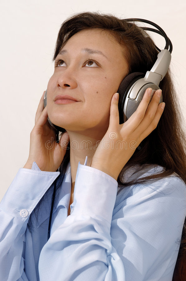 Girl in a blue shirt with headphones. A portrait of a beautiful, smiling, young asian girl in a blue shirt with headphones listening to the music on the radio royalty free stock image