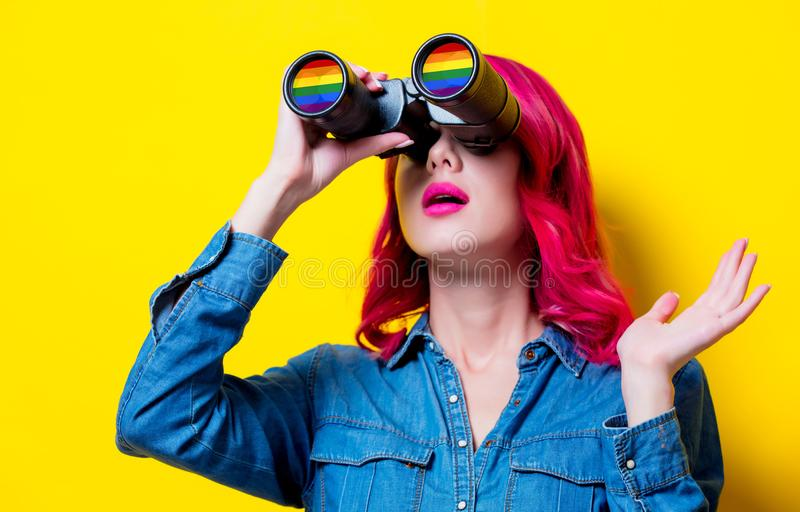 Girl in blue shirt holding binoculars with rainbow stock images