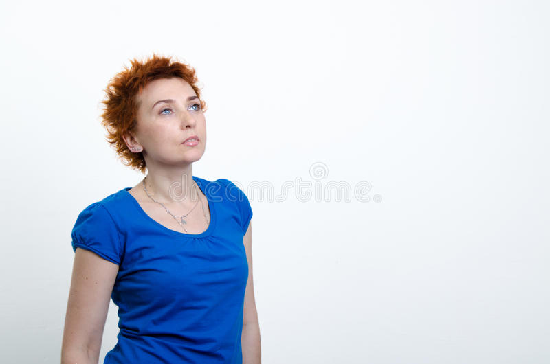Girl in a blue shirt. Young woman on a white background in a blue shirt stock images