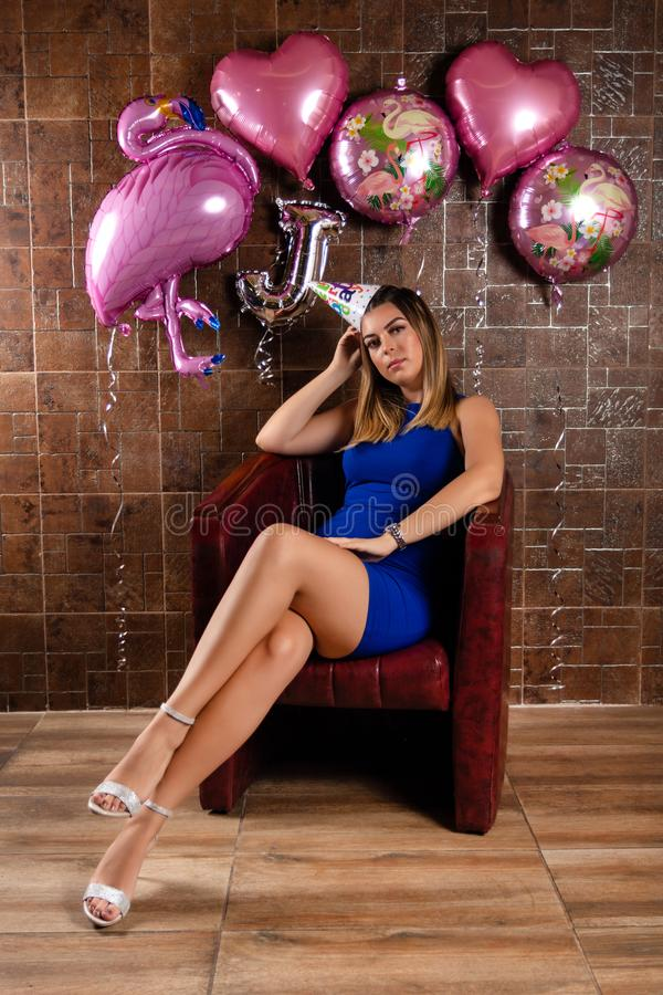 Girl in a blue short elegant dress and birthday cap on head sitting in a red chair. And decorative wall in the background in the restaurant. Birthday party stock image