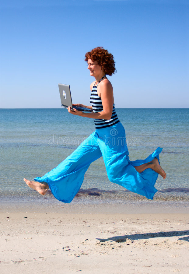 Girl in blue trousers running with laptop