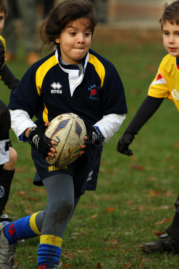 Girl with blue/yellow jacket play rugby