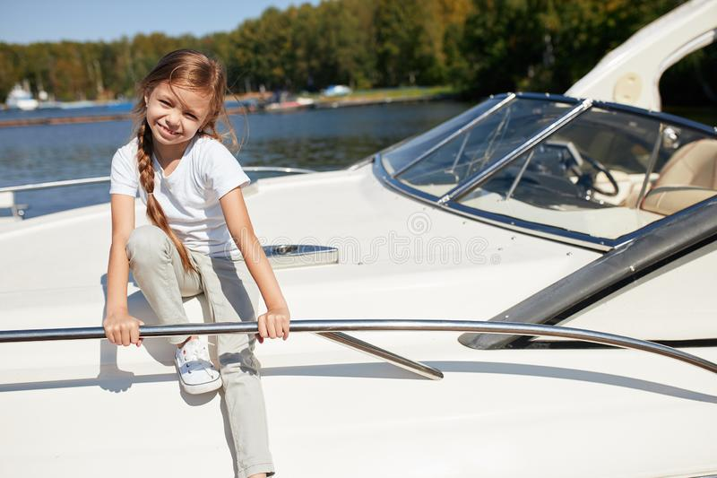 Girl on boat deck sails on summer day. Little girl on boat deck sails on summer day stock photos