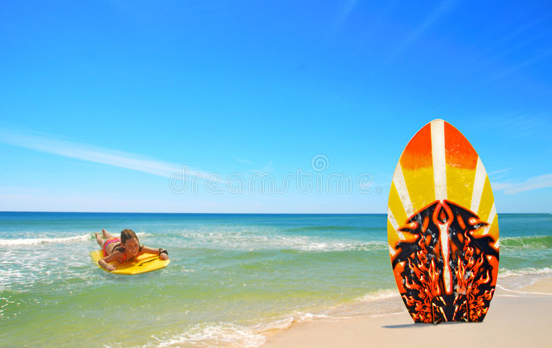 Girl body surfing towards board at beach. Young girl body surfing towards surf board in sand at pretty beach royalty free stock photo
