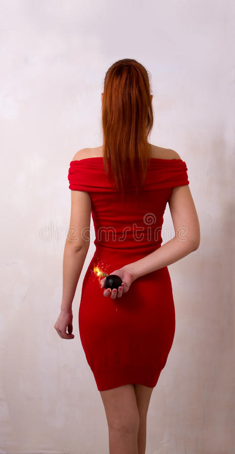 Girl With Bomb. Intelligent looking girl in red dress holding behind the back of bomb with burning wick royalty free stock photography