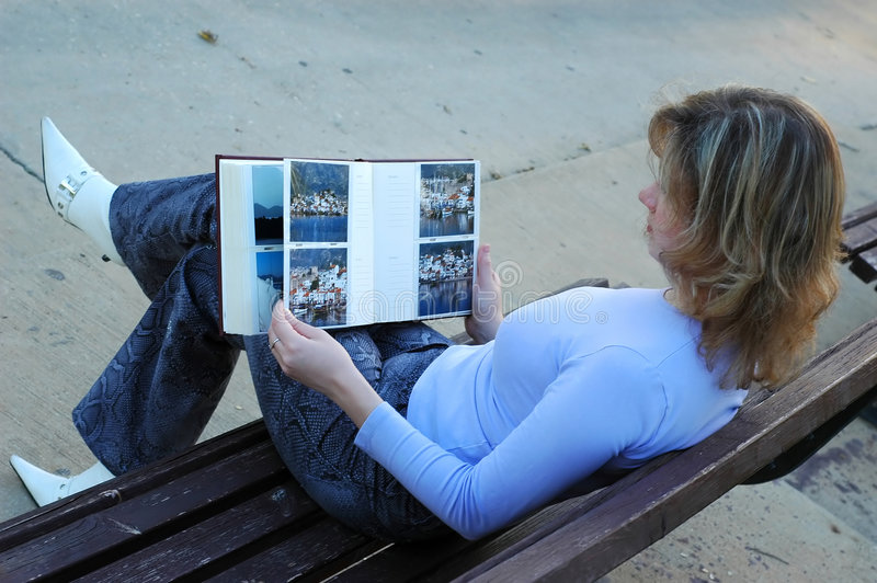 Girl with book. Attractive girl flips through photo album on a bench in park. Images in the album are copyrighted by same photografer as current image royalty free stock photo