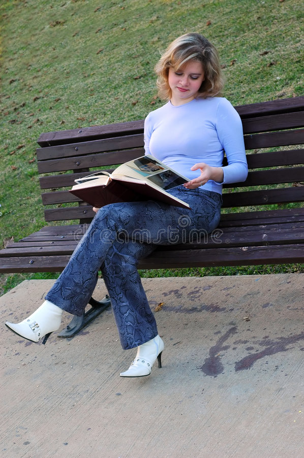 Girl with book. Attractive girl flips through photo album on a bench in park. Images in the album are copyrighted by same photografer as current image royalty free stock photos