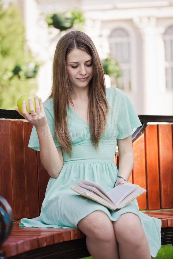 Girl with book and aple outdoors